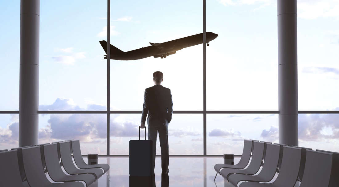 A man on a suit holding its suit case, standing in an airport watching an airplane flying.