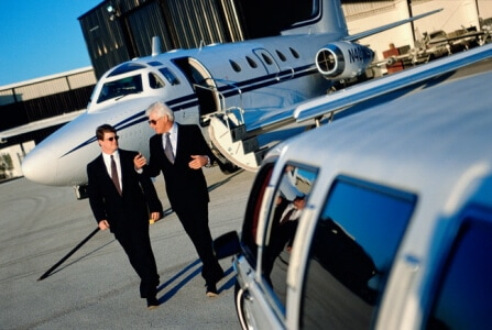 Two man on a suit walking away on airplane and approaching a limousine shuttle.
